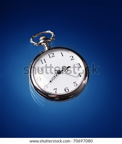 An old pocket watch on blue background - stock photo