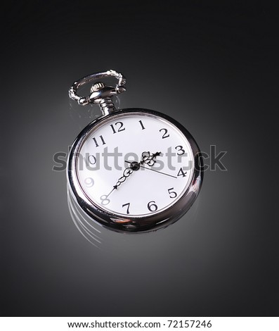 An old pocket watch on dark background - stock photo