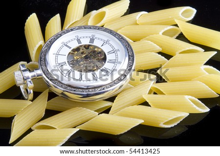 An old pocket watch on some italian pasta - stock photo