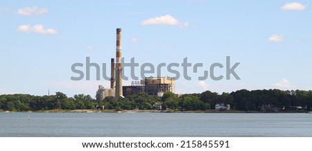 An old power plant/oil refinery along the shoreline of the York river in Yorktown Virginia as seen from the USCG training center pier on a summer day