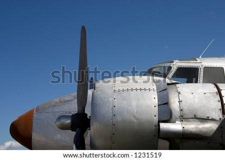 An old prop plane against a blue sky.