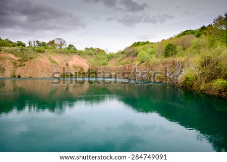 An old quarry filled up with water surrounded by trees - stock photo