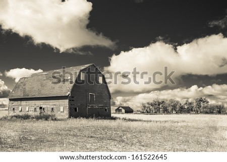 An old red barn on a farm. Taken with an infrared monochrome sepia filter. - stock photo