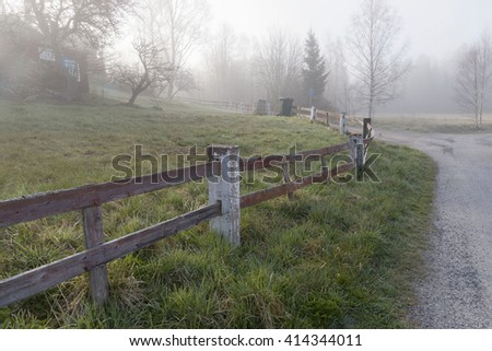 An old red fence at the country road a foggy morning during spring - stock photo