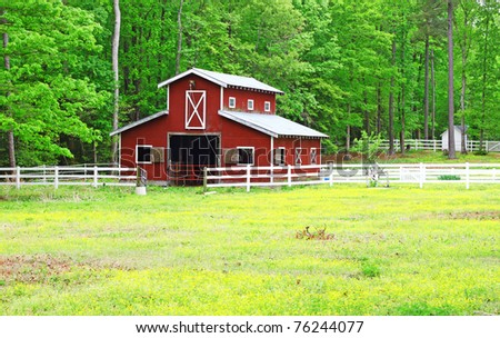 An old red horse barn in the woods among a buttercup field field during a spring day - stock photo