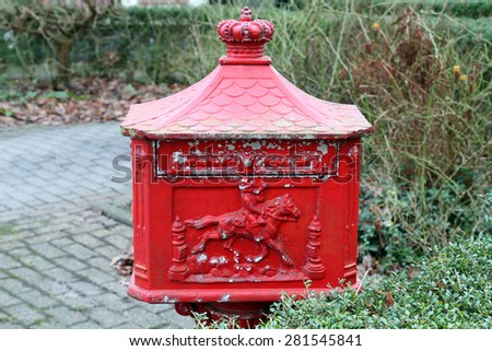 An old red iron mailbox in a garden.  - stock photo
