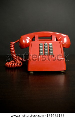 An old red telephone with gray push buttons. - stock photo
