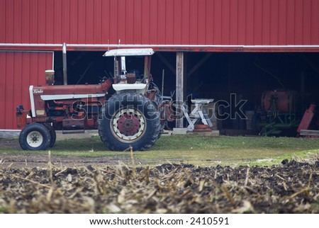 An old red tractor by a barn
