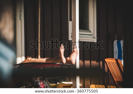 An old retired senior man is relaxing and sunbathing on the porch of his summer house. He is enjoying the quality of life after many years of hard work.  - stock photo