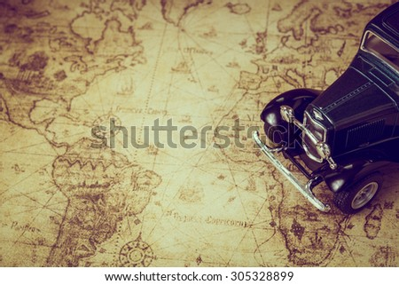 An old retro car on a treasure map background - stock photo