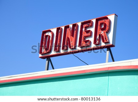 An old retro diner sign on top of a building. - stock photo