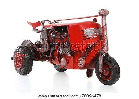 An old retro red tractor over a white background