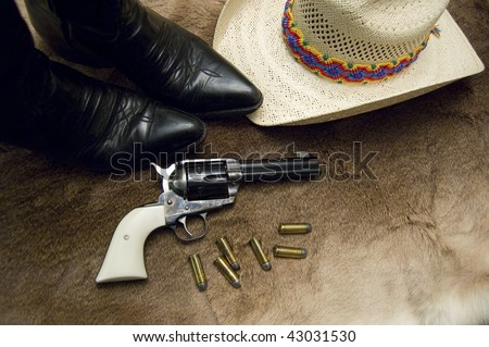 An old revolver with black boots and a hat on top of an old deer skin