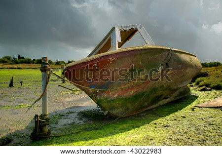 An old, rotting boat, moored at the side of a tidal inlet of Poole Harbour, Dorset (UK) - stock photo