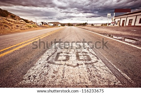 An old Route 66 shield painted on road - stock photo