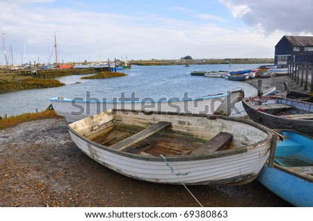 An old rowing boat drawn up on the shore of a sheltered harbour - stock photo