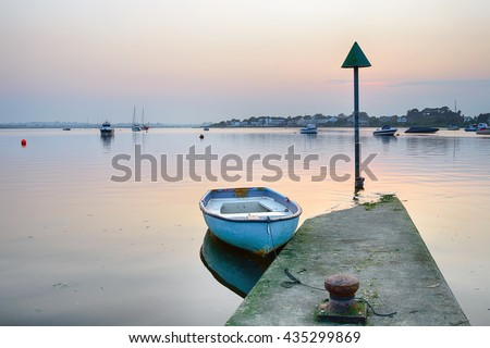 An old rowing boat on a jetty at Mudeford Quay in Christchurch in Dorset - stock photo