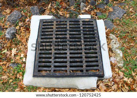 An old rusted and cracked cast iron storm drain for storm water runoff in the ground. - stock photo