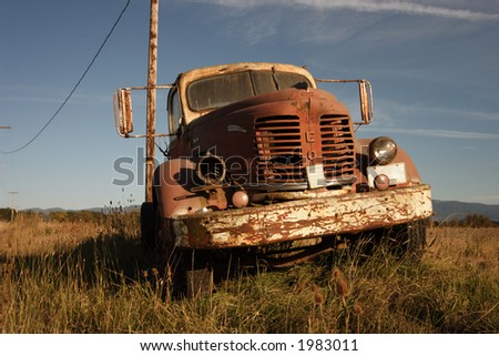 An old rusted farm truck in a field. - stock photo