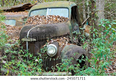 An old rusted out scrap truck that has been abandoned in the woods  - stock photo