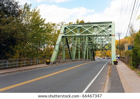 An old rusted steel bridge in a New England suburban town.