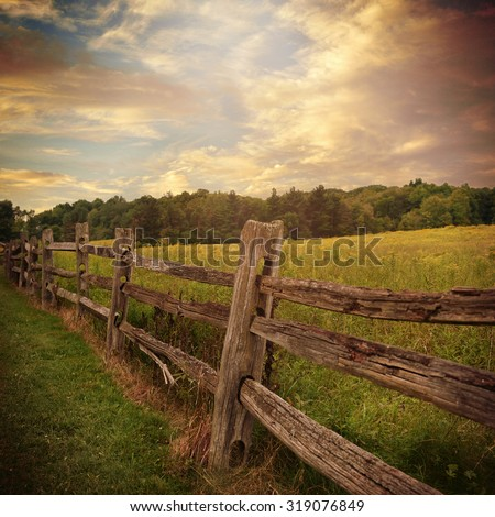 An old rustic wooden fence is in a grass filed with trees and clouds in the background for a country or nature concept. - stock photo