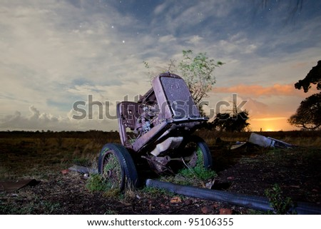 An old rusting away tractor shot at night with light painting technique. High iso long exposure some un avoidable noise present. - stock photo