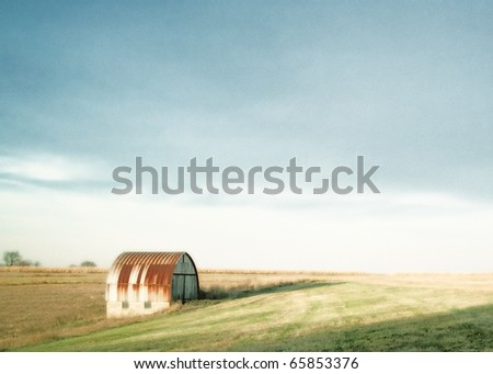 An old rusty barn or shed sitting in the middle of a barren field in what is a pastoral autumn setting. - stock photo