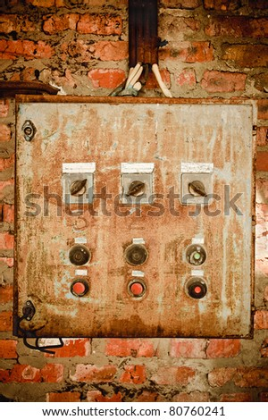 An old rusty control panel on the brick wall