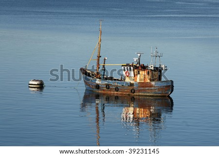 An old rusty fishing boat at anchor in Oban Bay, Scotland - stock photo