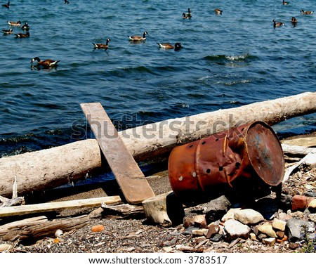 An old rusty 55-gallon drum is knocked over on its side mere inches from the waters of Lake Erie - stock photo