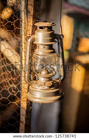 An old rusty oil lamp hanging on a wood fence - stock photo