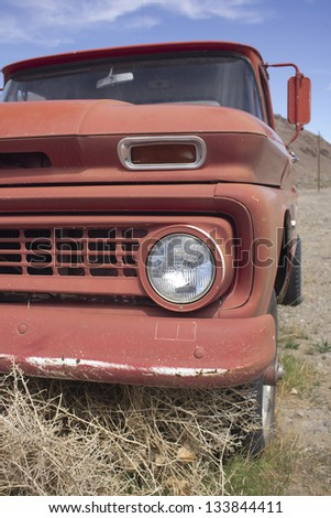 an old rusty pickup truck in the desert. Blue skies and tumbleweeds. - stock photo
