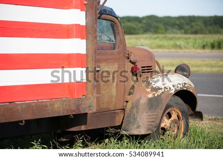 An old rusty truck adorned with an American Flag paint job.