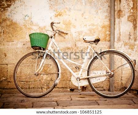 An old, rusty white bicycle with a basket leaning against a grungy wall in Italy. - stock photo