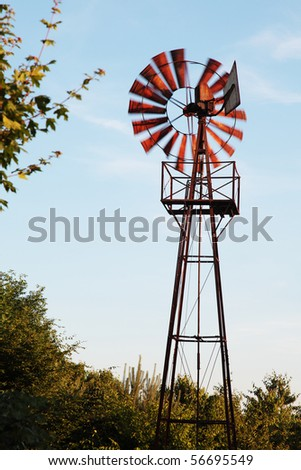 An old rusty windmill spinning in the wind, the blades are motion blurred