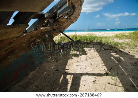 An old sailboat decays on a white sand beach in the Caribbean. - stock photo