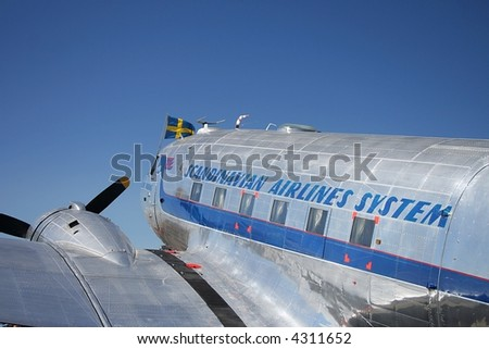 An old Scandinavian Airline System DC-3 airplane. With a Sweedish flagg in the front. - stock photo