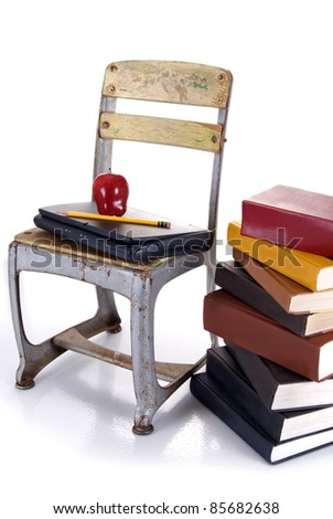 An old school chair holding a laptop with an apple and pencil on top beside a stack of hardbound books on a white background with reflection. - stock photo