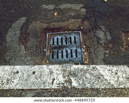 an old sewer manhole in a ruined street - stock photo