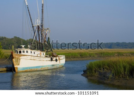 An old shrimp boat docked in a marshy grassland - stock photo