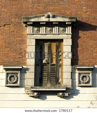An old shuttered window with ornate marble decorations hints at it's former glory. - stock photo