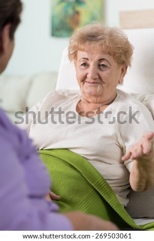 An old sick woman talking to her friend from bed - stock photo