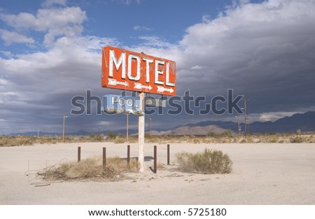 An old sign overlooking undeveloped desert land. - stock photo
