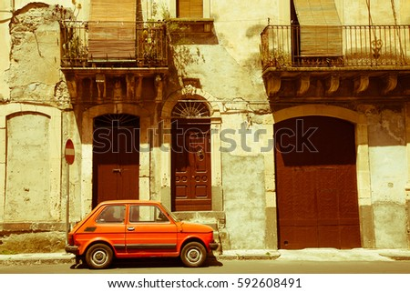 An old small car standing on a street in front of antique houses in the town of Militello in Val di Catania of southern Sicily, Italy - vintage