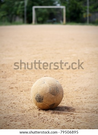 An old soccer ball on ground, goal is the background - stock photo
