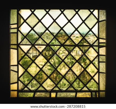 An old stained glass window with pigmented window panes and leaded glass distorts the French countryside into a a view that looks like an impressionist painting. - stock photo