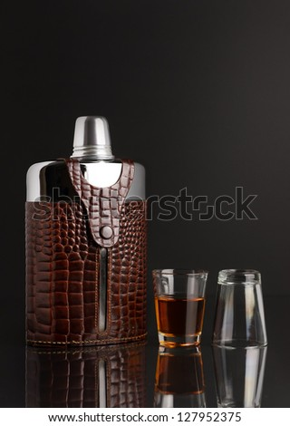 An old stainless steel vintage flask, with a leather holder and two shot glasses. - stock photo