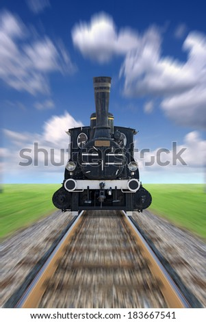 An old steam powered locomotive, railway track, green grass and blue sky blurred - stock photo