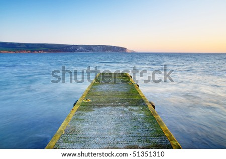 An old stone jetty and a tranquil sea - sunrise in Swanage, Dorset (UK) - stock photo